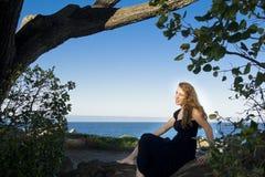 muchacha que pasa por alto la bahía de monterey bajo un árbol Foto de archivo libre de regalías