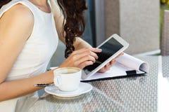 Muchacha que pasa tiempo en un café usando la tableta digital Foto de archivo libre de regalías