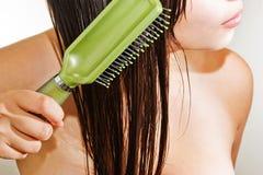 Muchacha que peina el pelo Imagenes de archivo