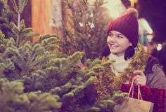 Muchacha que permanece en el mercado entre los árboles de navidad Fotografía de archivo libre de regalías