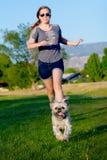 Muchacha que persigue el pequeño perro Fotos de archivo libres de regalías