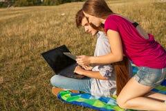 Muchacha que pide a su amigo ayuda con su PC de la tableta Foto de archivo libre de regalías