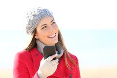 Muchacha que piensa con un teléfono en invierno Imagen de archivo