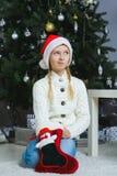 Muchacha que piensa en los regalos para la Navidad o nueva Foto de archivo