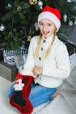 Muchacha que piensa en los regalos para la Navidad o nueva Imagenes de archivo