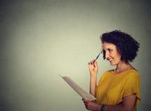 Muchacha que piensa haciendo los planes que anotan ideas Imagen de archivo libre de regalías