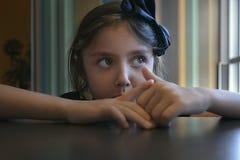 Muchacha que piensa y que se sienta en la tabla foto de archivo