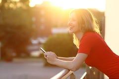 Muchacha que piensa y que sostiene un teléfono elegante en la puesta del sol Imagenes de archivo