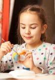 Muchacha que pinta los huevos de Pascua tradicionales en casa Imagenes de archivo