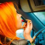 Muchacha que pinta sus labios que hacen maquillaje mientras que conduce el coche Imagenes de archivo