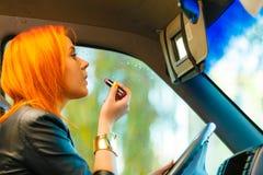 Muchacha que pinta sus labios que hacen maquillaje mientras que conduce el coche Imagen de archivo
