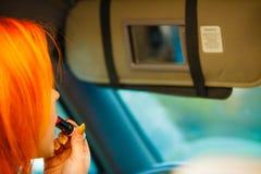 Muchacha que pinta sus labios que hacen maquillaje mientras que conduce el coche Fotos de archivo libres de regalías