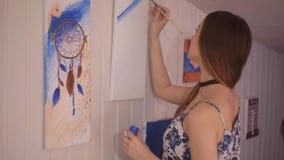 Muchacha que pinta una imagen en el estudio casero Mujer modelo que pinta su imagen Arte La mujer dibuja las pinturas Muchacha co almacen de video