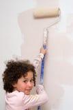 Muchacha que pinta una pared Imagen de archivo libre de regalías
