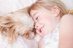 Muchacha que pone con el perro del tzu del shih Foto de archivo libre de regalías
