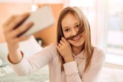 Muchacha que pone el filamento del pelo debajo de nariz mientras que toma el selfie Foto de archivo libre de regalías