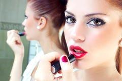 Muchacha que pone el lápiz labial en sus labios Imagenes de archivo