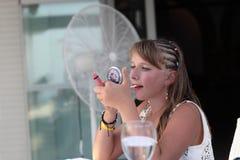 Muchacha que pone el lápiz labial en sus labios Fotografía de archivo