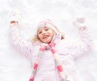 Muchacha que pone en el ángel de fabricación de tierra de la nieve Fotografía de archivo