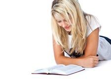 Muchacha que pone en el libro del suelo y de lectura Imágenes de archivo libres de regalías