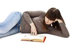 Muchacha que pone en el libro del suelo y de lectura Fotos de archivo libres de regalías
