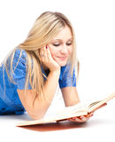 Muchacha que pone en el libro del suelo y de lectura Foto de archivo libre de regalías