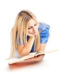 Muchacha que pone en el libro del suelo y de lectura Fotografía de archivo libre de regalías
