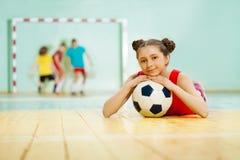 Muchacha que pone en el piso del pasillo de deportes con la bola Fotografía de archivo libre de regalías