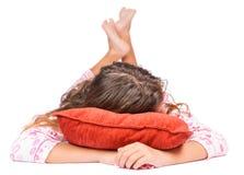 Muchacha que pone en el piso que lleva sus pijamas Imagen de archivo