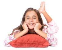 Muchacha que pone en el piso que lleva sus pijamas Fotografía de archivo