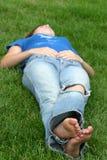 Muchacha que pone en hierba Imagen de archivo