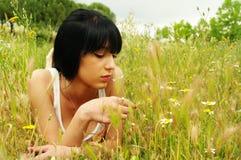 Muchacha que pone en hierba Fotografía de archivo