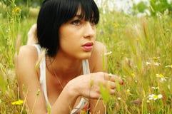 Muchacha que pone en hierba Fotografía de archivo libre de regalías