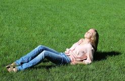 Muchacha que pone en hierba Fotos de archivo libres de regalías
