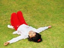 Muchacha que pone en hierba Imagenes de archivo