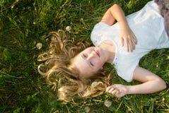 Muchacha que pone en hierba con los dientes de león Foto de archivo libre de regalías