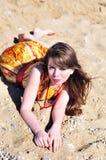 Muchacha que pone en la arena Fotografía de archivo