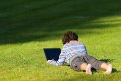 Muchacha que pone en la hierba con Imagen de archivo