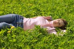 Muchacha que pone en la hierba, sonriendo. Fotos de archivo libres de regalías
