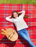 Muchacha que pone en la tela escocesa a cuadros al lado de cesta de mano Fotos de archivo