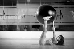 Muchacha que pone en piso del gimnasio Foto de archivo libre de regalías