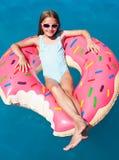 Muchacha que pone en un buñuelo inflable colorido Imagenes de archivo