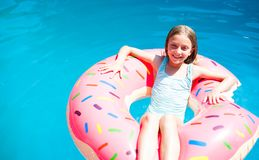 Muchacha que pone en un buñuelo inflable colorido Fotografía de archivo