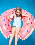 Muchacha que pone en un buñuelo inflable colorido con una bebida Foto de archivo