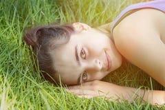 Muchacha que pone en un prado Fotos de archivo