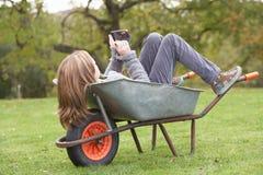 Muchacha que pone la carretilla usando el teléfono elegante Imagen de archivo