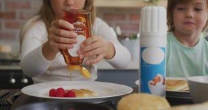 Muchacha que pone la miel en la crepe en la mesa de comedor en un hogar cómodo 4k metrajes