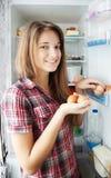 Muchacha que pone los huevos en refrigerato Imágenes de archivo libres de regalías