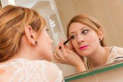 Muchacha que pone maquillaje Fotos de archivo libres de regalías