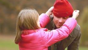 Muchacha que pone su casquillo en la cabeza del papá metrajes